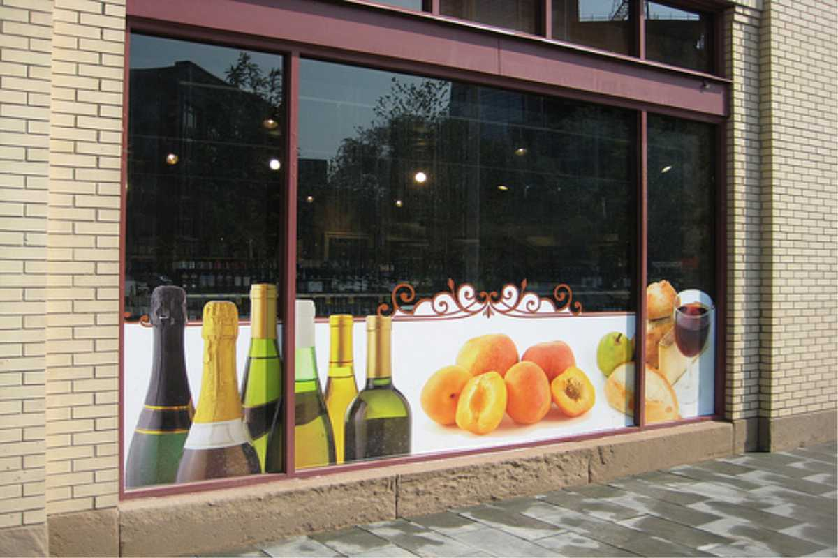 large format digital printing in window of wine shop with bottles and fruit